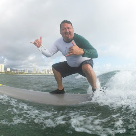 Owner and Instructor, John, of Polu Lani Surf catching a wave throwing a double shaka!