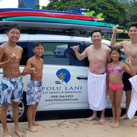 Family of 5 throwing shakas in front of the Polu Lani Surf van after a private surfing lesson. Provided by Polu Lani Surf