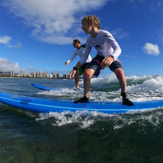Photo of a father and son riding the same wave. Provided by Polu Lani Surf