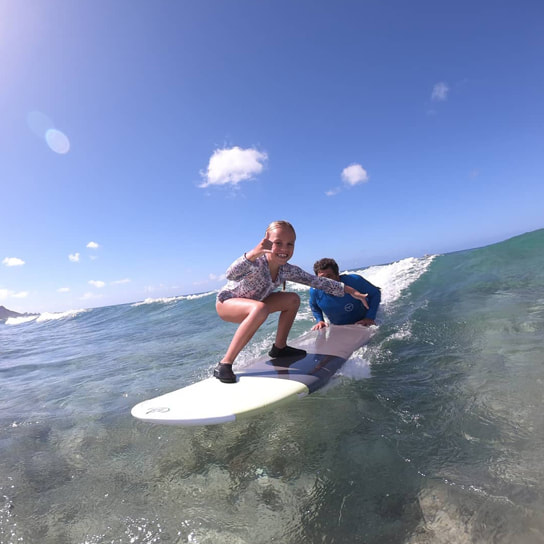 Instructor John and young girl catching a wave together. Provided by Polu Lani Surf