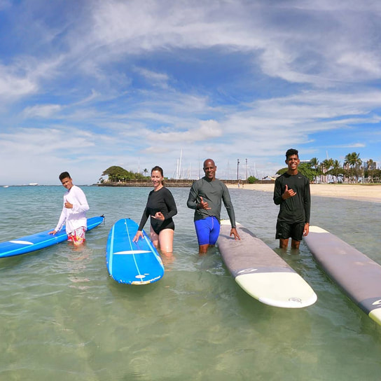 Family of 4 throwing shakas about to start their private surfing lesson. Provided by Polu Lani Surf